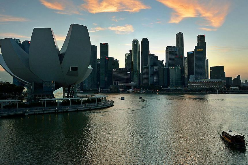 Bumboats travelling on Marina Bay with the skyline of the ArtScience Museum (left) and the Marina Bay financial district as the background.-- PHOTO: ST FILE