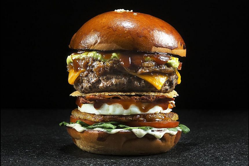 The Works is a substantial burger with baby spinach, bacon weave, rosti potatoes, parmesan crisp, onion ring, fried egg, sliced tomatoes, beer-caramelised onions and guacamole. -- PHOTO: WILDFIRE KITCHEN + BAR