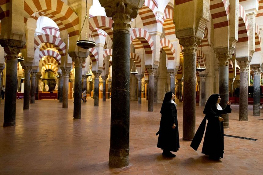 Nuns visit the Mosque-Cathedral of Cordoba on Oct 14, 2014. The Spanish city of Cordoba boasts that different faiths have long co-existed there, but locals are now squabbling over its star tourist attraction: a cathedral that was once a mosque. -- PH