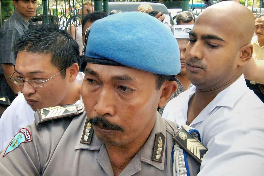 Convicted Australian drug smugglers Myuran Sukumaran (left) and Andrew Chan (right) are escorted by an Indonesian policeman to a court trial in Denpasar, Bali on Feb 14, 2006. -- PHOTO: AFP