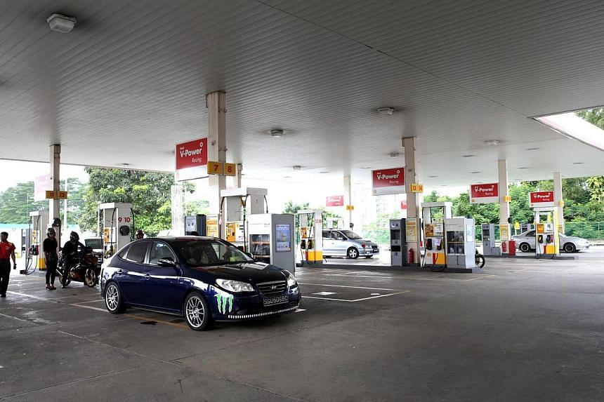 Cars topping up their fuel tanks at a Shell petrol station. Petrol prices fluctuated on Friday, with at least three firms adjusting some of their prices from Thursday. As of 4pm on Friday, only prices at Esso remained unchanged. -- ST PHOTO: CHE