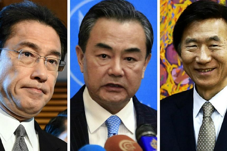(From left) Japanese Foreign Minister Fumio Kishida and his counterparts Wang Yi of China and Yun Byung Se of South Korea will meet in Seoul in late March, the Yomiuri Shimbun reported. -- PHOTO: AFP / REUTERS / EPA