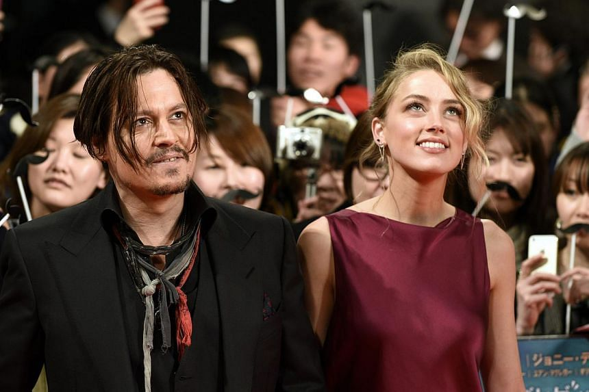 US actor Johnny Depp (left) and partner US actress Amber Heard arrive for the premiere of Mortdecai in Tokyo, Japan, on Jan 27, 2015. -- PHOTO: EPA