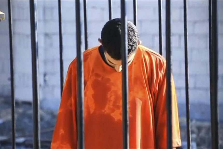 A man purported to be Islamic State captive Jordanian pilot Muath al-Kasaesbeh is seen standing in a cage in this still image from an undated video filmed from an undisclosed location made available on social media on Feb 3, 2015. -- PHOTO: REUTERS