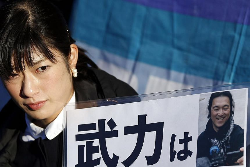 A woman holding a portrait of Japanese journalist Kenji Goto on a placard during a rally against Japan's Prime Minister Shinzo Abe in Tokyo on Feb 1, 2015. -- PHOTO: REUTERS