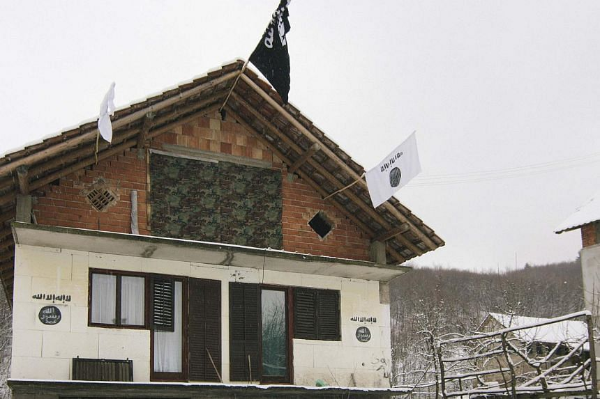 A house in the Bosnian village of Gornja Maoca decorated with Islamic State flags, Jan 26, 2015. -- PHOTO: REUTERS