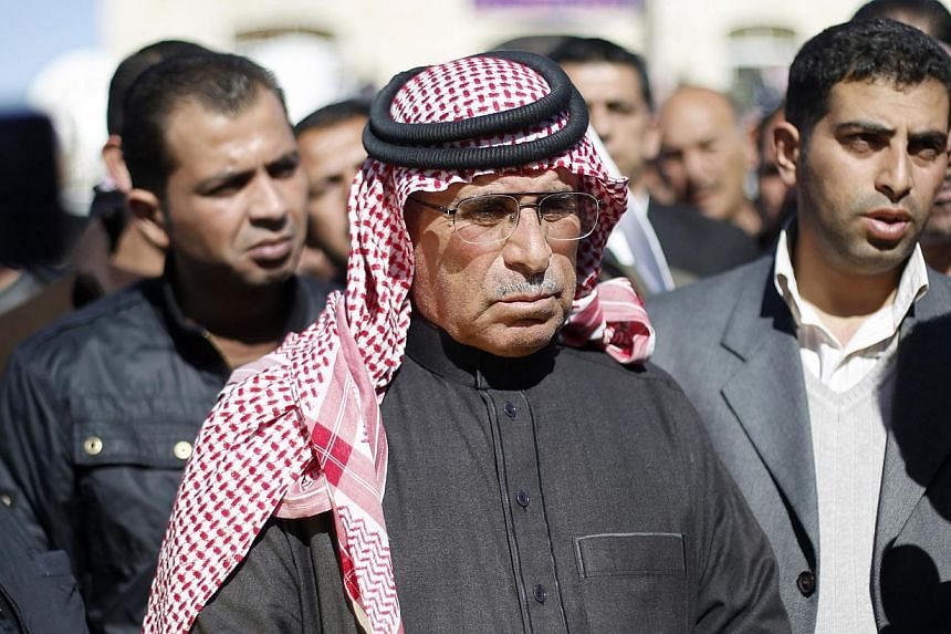 Father of Jordanian pilot Muath al-Kasaesbeh, Saif (centre), is seen at the headquarters of the family's clan in Karakcap. The burning of his son in a cage and filming of it have drawn denunciations across the Arab and Islamic world.