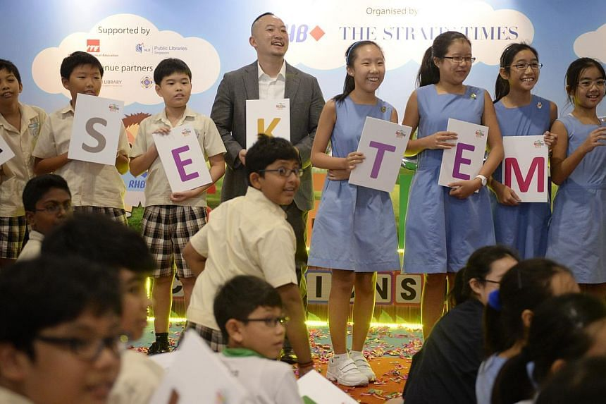 Singapore Chinese Girls' School Primary 6 students (right) with Primary 5 Yishun Primary School students (left) during a round of the fun spell-off where they had to spell the word Temasek with The Straits Times managing editor Ignatius Low at