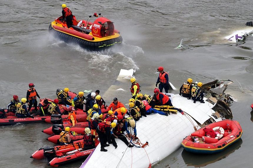 Search and rescue team members operate on a TransAsia Airways passenger plane that crashed into the Keelung River in Taipei on 04 February 2015. -- PHOTO: EPA