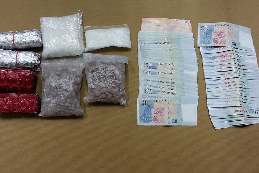 Drugs and cash seized from one of the operations CNB launched to take down the syndicate on Oct 30, 2014. -- PHOTO: CENTRAL NARCOTICS BUREAU