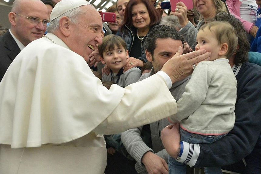 Pope Francis greets a child during a general audicence in the Vatican City on Jan 28, 2015. -- PHOTO: EPA