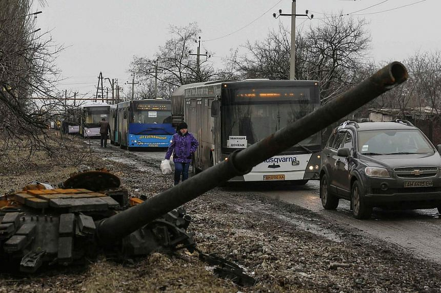 Empty buses, intended for internally displaced persons (IDPs), wait along a road beside a burnt-out tank turret while travelling in the direction of the village of Debaltseve to evacuate the residents, in Vuhlehirsk, Donetsk region on Feb 6, 2015.&nb