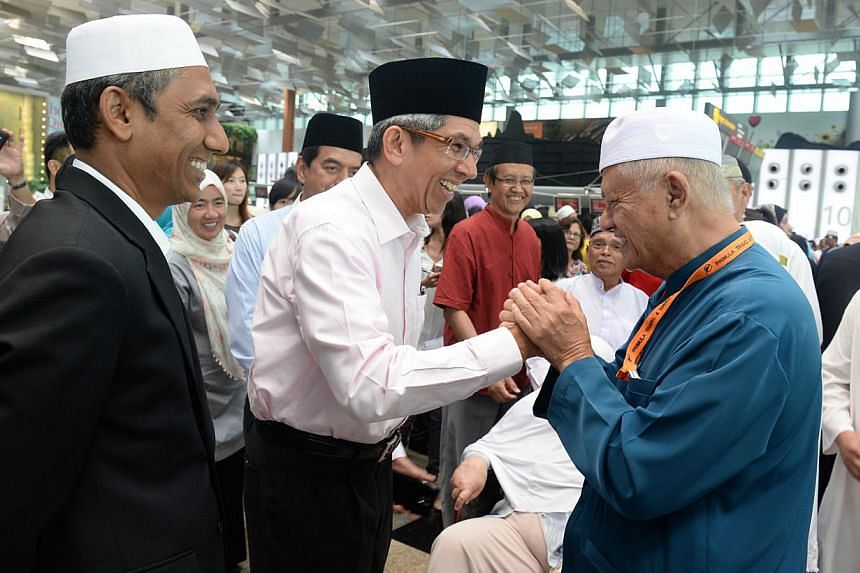 Minister-in-charge of Muslim Affairs Yaacob Ibrahim speaking to former MP Wan Hussin Zoohri at Changi Airport on Sep 26, 2014, before the latter's departure to Mecca. An increase in the Hajj quota would help the many Singaporeans on the waiting lis