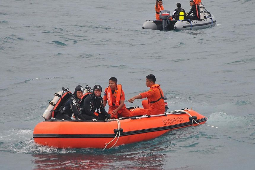 In this Feb 2, 2015 photo, Indonesian divers and rescue personnel from the National Search and Rescue Agency recover a body from the underwater wreckage of the ill-fated AirAsia flight QZ8501 in the Java sea. -- PHOTO: AFP