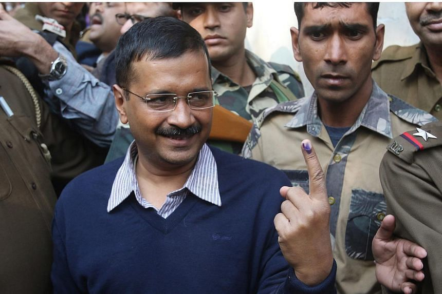 Aam Admi Party's (AAP) Chief Ministerial candidate Arvind Kejriwal shows his ink-marked finger after casting his vote at a polling station in New Delhi, India, Feb 7, 2015. India's Narendra Modi was forecast to suffer the first major setback of his p