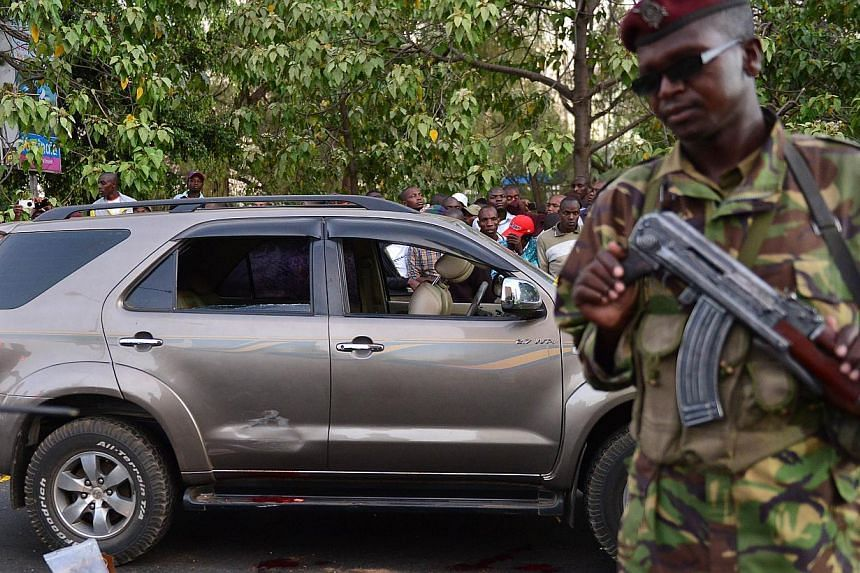 A police officer stands near the blood stained vehicle of prominent government MP Hon George Muchai after he was shot dead by gunmen early morning in Nairobi, on Feb 7, 2015, along with his two bodyguards and driver according to a senior police offic