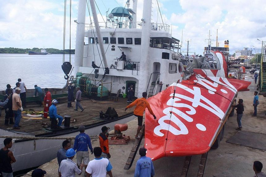 Workers load the tail of AirAsia flight QZ8501 onto a truck at Kumai sea port, in Central Kalimantan on Feb 7, 2015, before they transport it to Jakarta. Indonesian divers have found a body believed to be French co-pilot Remi Plesel, who was steering