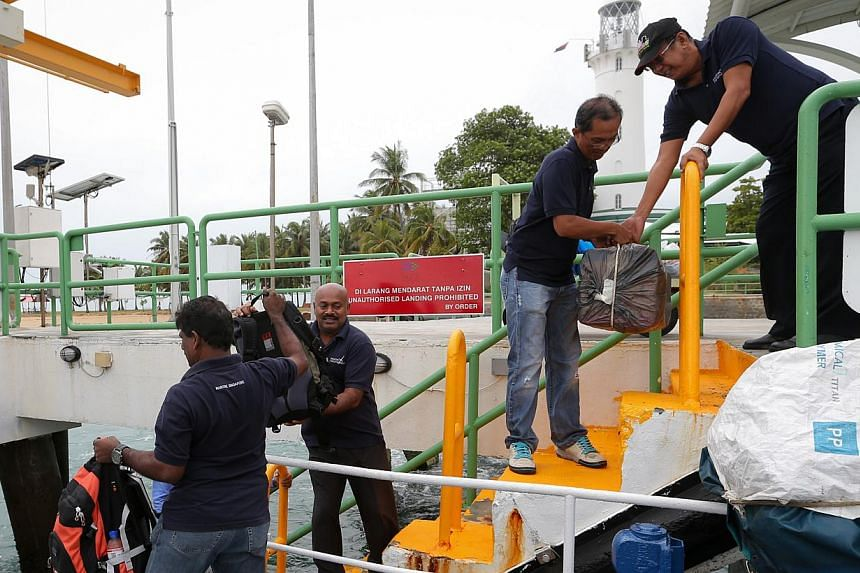 (Top) Mr V. Uthrapathi (left) taking over duties from Mr Syed Hassan, 66, at Raffles Lighthouse. (Above) Belongings being loaded and unloaded from a boat at the jetty as Mr Uthrapathi (from left) and his assistant N. Manikaveloo, 51, prepare to spend