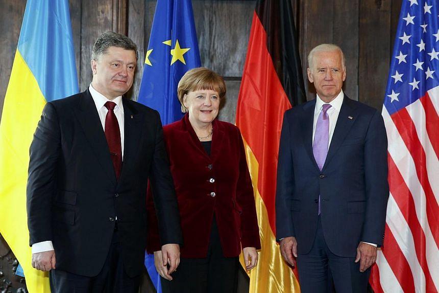 Ukraine's President Petro Poroshenko (left), German Chancellor Angela Merkel and US Vice-President Joe Biden pose during the Munich Security Conference on Feb 7, 2015. -- PHOTO: REUTERS