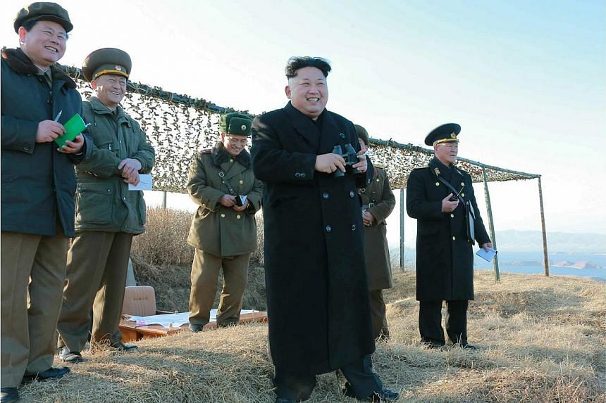An undated handout picture released by the official North Korean Central News Agency (KCNA) on Feb 7, 2015 shows North Korean leader Kim Jong-un watching the test-firing of a new anti-ship rocket at an undisclosed location. -- PHOTO: EPA