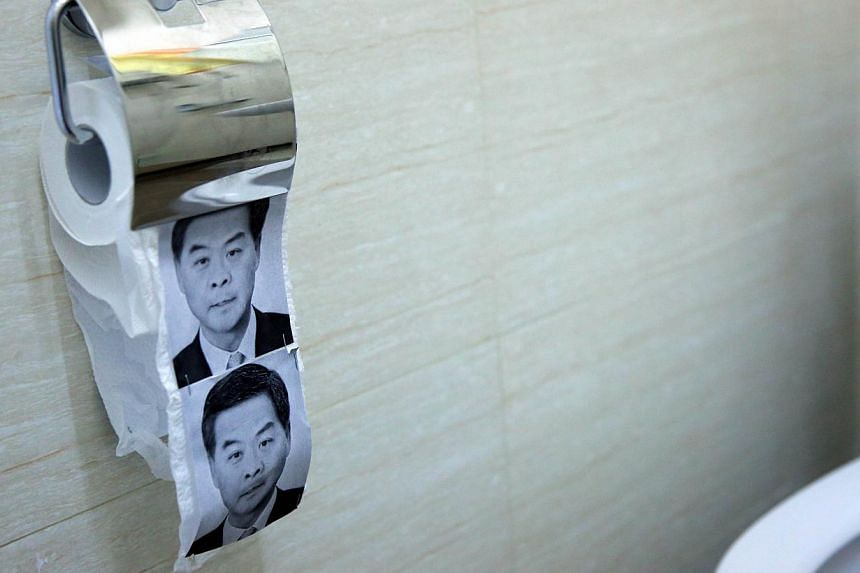 This photo taken on Dec 23, 2014 shows novelty toilet paper with the image of Hong Kong's Chief Executive Leung Chun-ying (right) in a flat turned into a recreation of the main pro-democracy protest site in Hong Kong. -- PHOTO: AFP