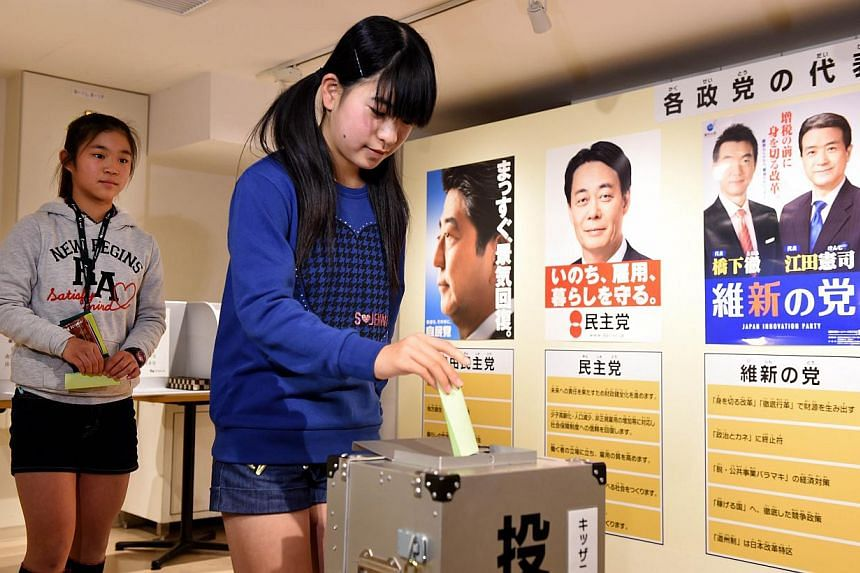 A girl casts her vote before posters of Japan's major parties, including ruling Liberal Democratic Party (LDP) leader and Prime Minister Shinzo Abe (back left), in a straw poll for the upcoming lower house election at the KidZania career theme park i