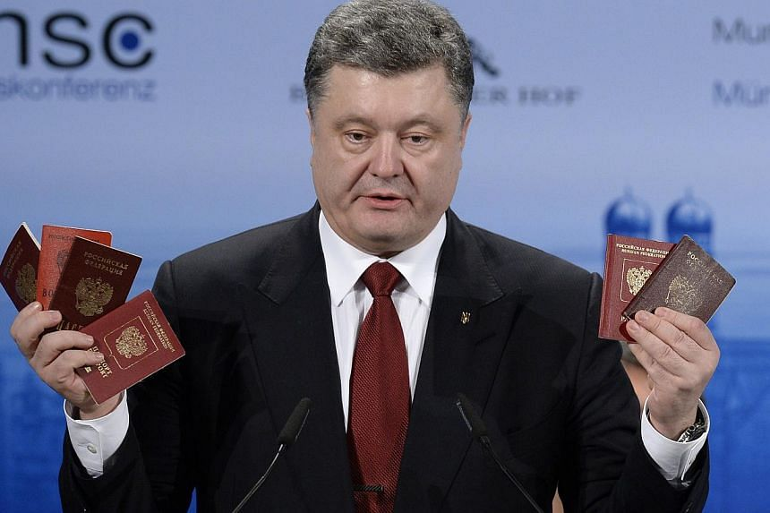 "Ukraine President Petro Poroshenko on Saturday brandished in front of world leaders several passports (above) taken from Russian soldiers in what he said was proof of Moscow's ""presence"" in his country. -- PHOTO: AFP"