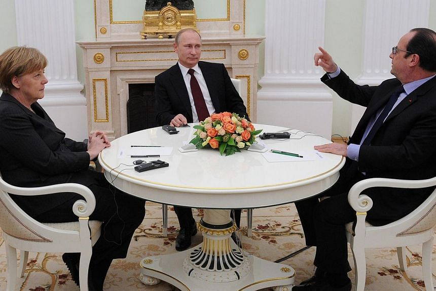 French President Francois Hollande (right) gestures as he speaks with Russian President Vladimir Putin (centre) and German Chancellor Angela Merkel during a meeting at the Kremlin in Moscow on Feb 6, 2015. -- PHOTO: AFP