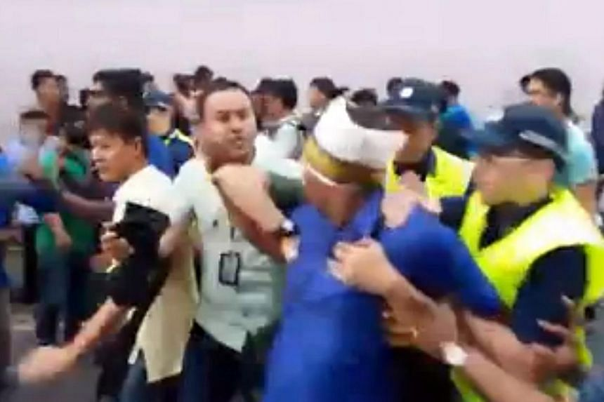 A screenshot of a video posted on Facebook showing a man being led away by police during a scuffle at the Thaipusam procession on Feb 3, 2015 .A 30-year-old Indian woman has filed a police report claiming that she was pushed and hit by cops dur