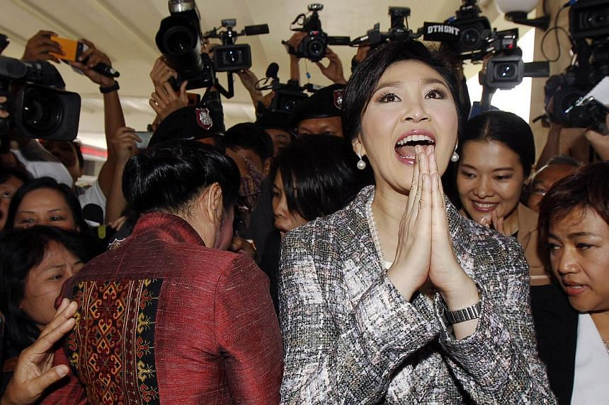 Ousted former Thai Prime Minister Yingluck Shinawatra giving a traditional greeting as she leaves parliament after delivering a statement during the National Legislative Assembly meeting in Bangkok, in this Jan 22, 2015, file photo. -- PHOTO: RE