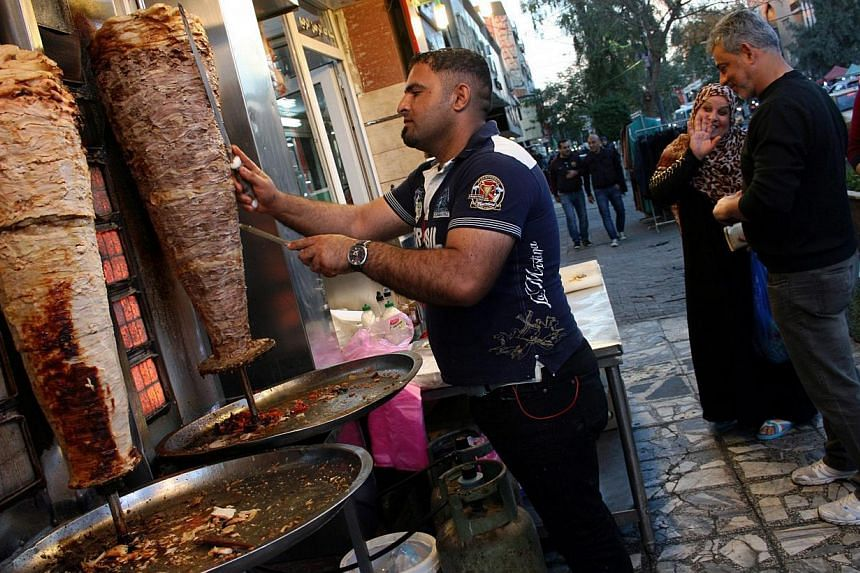 An Iraqi vendor sells shawarma at a restaurant in central Baghdad Feb 7, 2015. Iraqi Prime Minister Haider al-Abadi announced that a decade-long nighttime curfew in the capital will be lifted on Feb 7. -- PHOTO: EPA