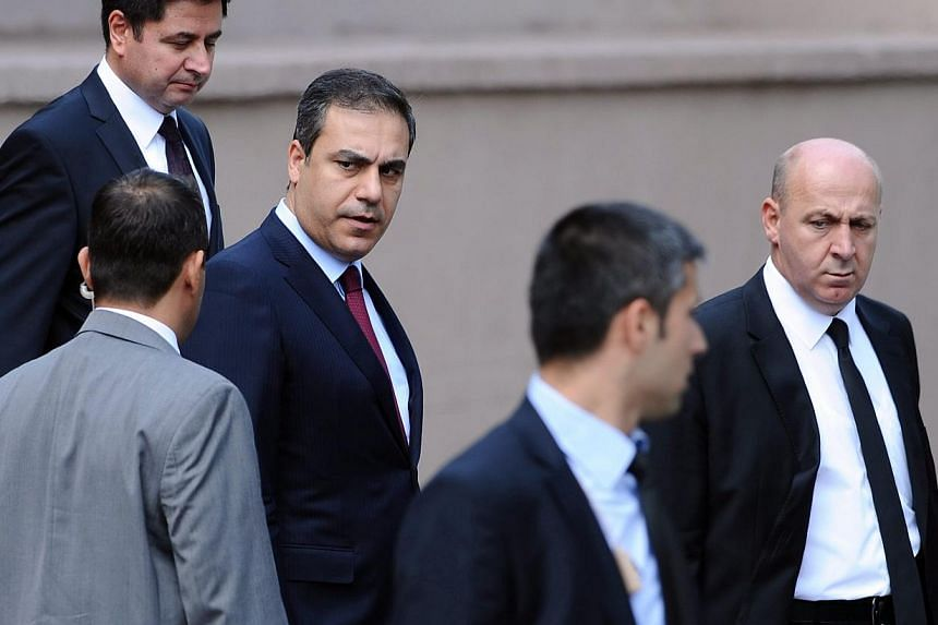 A 2012 file photo made available on Feb 7, 2015, shows the head of Turkey's intelligence service, Hakan Fidan (centre) in Ankara, Turkey. -- PHOTO: EPA