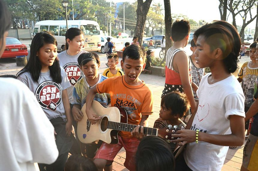 Ricky Nieco (right), 19, was a street child when he was five till his grandmother plucked him out of the streets when he turned seven. He now volunteers for Childhope Philippines, the non-profit organisation helping children who live off Manila's mea