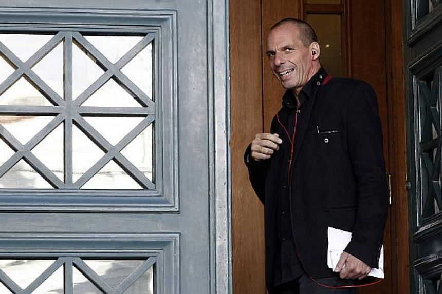 Greece's Finance Minister Yanis Varoufakis speaks on his phone upon arriving for a government meeting at the parliament building in Athens Feb 7, 2015. -- PHOTO: REUTERS