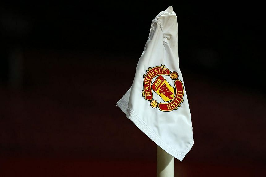 "The Manchester United club logo is seen on a corner flag on the Old Trafford pitch. A player from from the club was allegedly filmed by team-mates as he and a woman engaged in a ""sex act"" in the toilets of a nightclub. -- PHOTO: REUTERS"