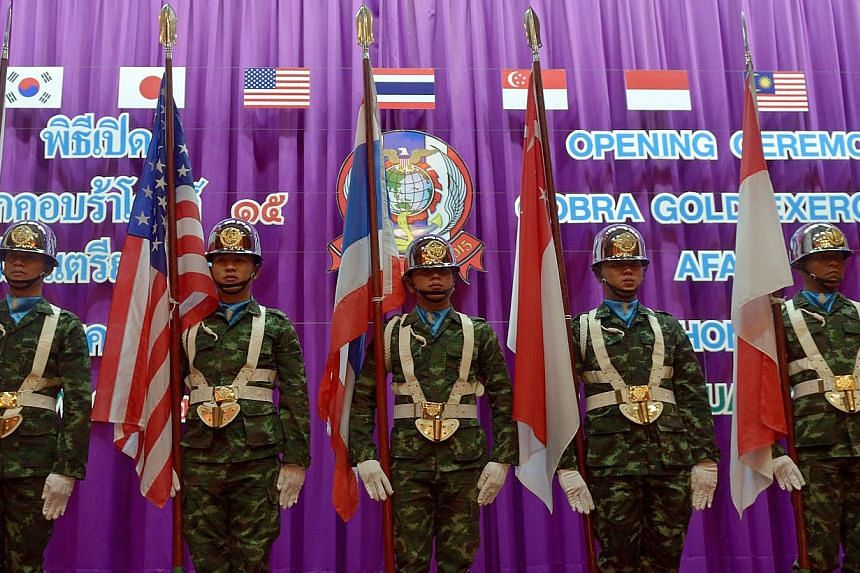Thai soldiers carry national flags of the participating nations as they parade during the opening ceremony for the annual combined military exercises coined Cobra Gold 15 at Armed Forces Academies Preparatory School in Nakhon Nayok province on Feb 9,