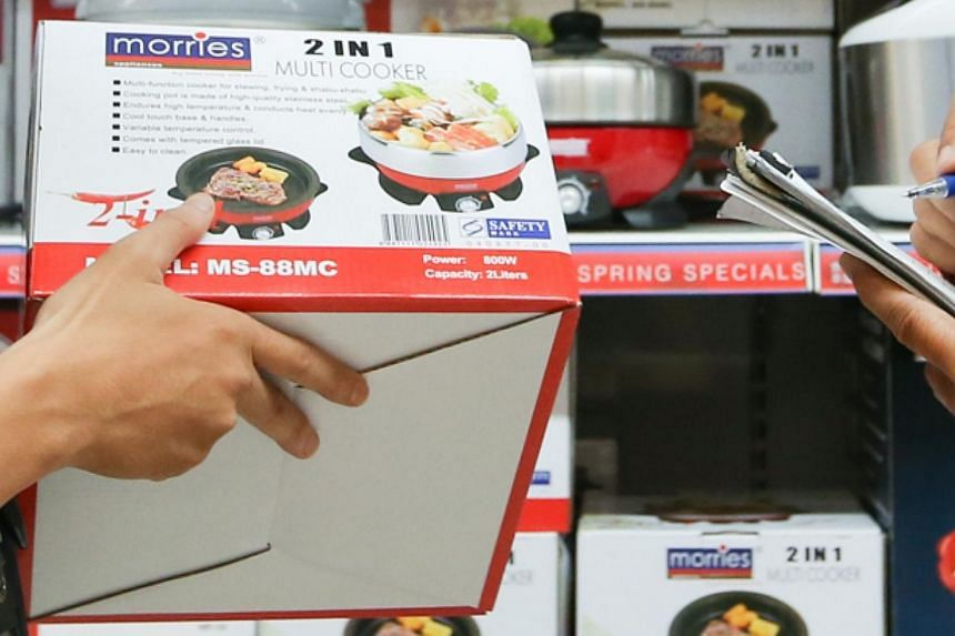 CERTIS Cisco enforcement officers checking for the Safety Mark sticker on electronic products sold in NTUC. Consumers who own electric bowls from the brands Nushi, T.M.D and T.A.C are advised to stop using them immediately if their appliances do