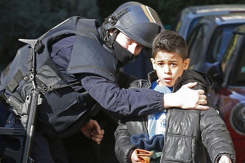 A French police officer speaks to a child as he secures an accessway to a school at the Castellane housing area in Marseille, on Feb 9, 2015. Hooded gunmen armed with Kalashnikov rifles fired on police in the French city, where Prime Minister Manuel