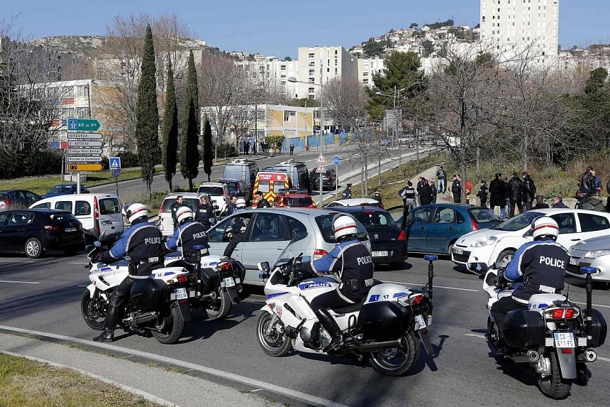 French police officers secure the access to the Castellane housing area in Marseille, on Feb 9, 2015.Hooded gunmen armed with Kalashnikov rifles fired on police in the French city, where Prime Minister Manuel Valls was paying a visit on Monday,