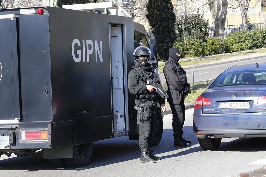 Members of the French National Police Intervention Groups (GIPN) stand guard near the 'Cite de la Castellane' northern Marseille, France, on Feb 9, 2015.Hooded gunmen armed with Kalashnikov rifles fired on police in the French city, where Prime
