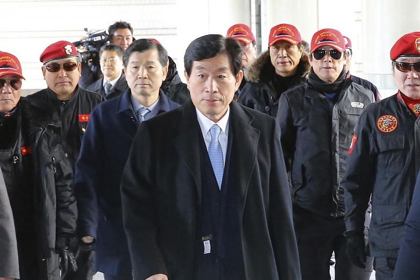 Won Sei-hoon (centre), former chief of South Korea's state intelligence agency, the National Intelligence Service (NIS), arrives at the Seoul High Court in Seoul on Feb 9, 2015. South Korea's former spy chief was jailed for three years Monday af