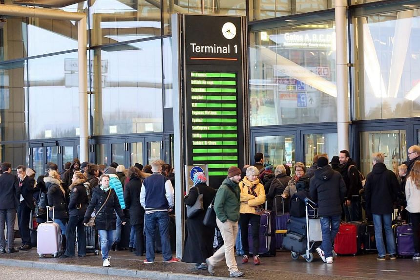 Passengers waiting at the entrance to Hamburg airport during strikes of airport security staff in Hamburg, Germany, on Feb 9, 2015. -- PHOTO: EPA