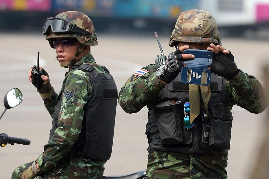 A Thai soldier taking picture of members of the media as they stand guard during a visit by Chaturon Chaisang, a former education minister, at an army base in Bangkok on Jan 29, 2015.Four people were lightly injured in a blast in an army ordnan