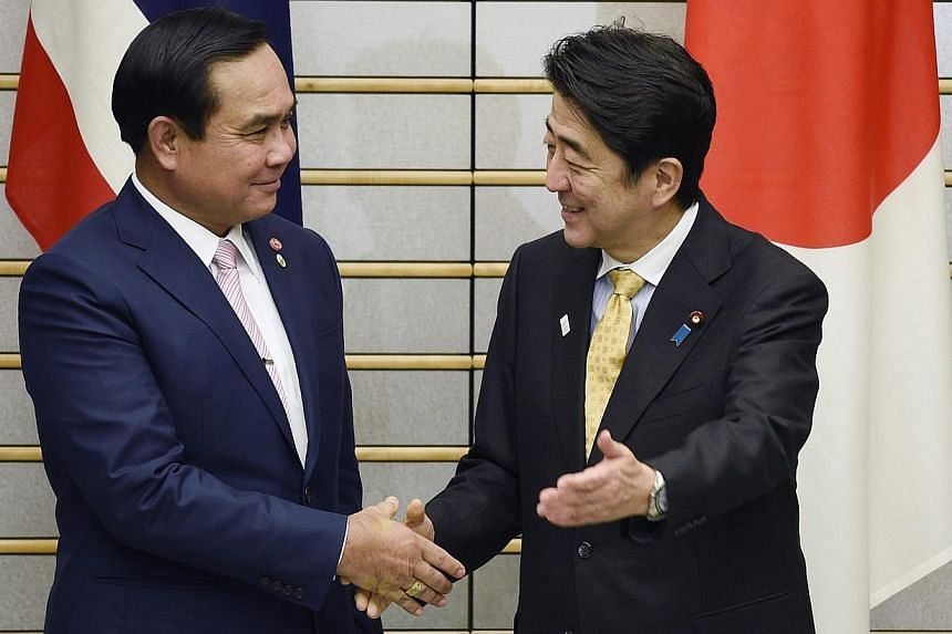 Thai Prime Minister Prayut Chan-o-cha (left) and Japanese Prime Minister Shinzo Abe shake hands prior to their meeting at Mr Abe's official residence in Tokyo, Japan on Feb 9, 2015.Mr Abe urged Thailand's military rulers to return as soon as po
