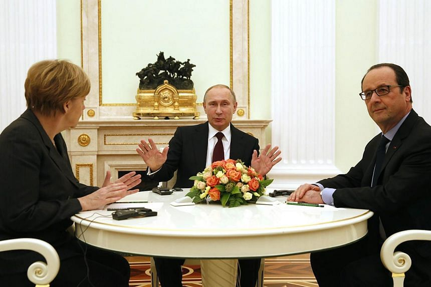 Russian President Vladimir Putin (centre) gestures as he speaks during a meeting with French President Francois Hollande (right) and German Chancellor Angela Merkel at the Kremlin in Moscow on Feb 6, 2015.Russia said on Monday, Feb 9, that its