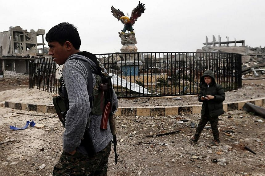 A young member of Syrian Kurdish People's Defence Units (YPG) patrols Kobane, Syria on Jan 30, 2015, after Islamic State in Iraq and Syria (ISIS) militants were pushed out of the city. Syria will not allow foreign ground troops on its territory