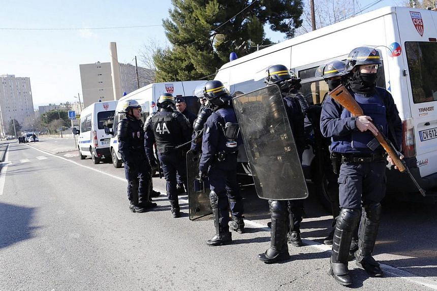 Members of the National Security forces (CRS) stand guard near the 'Cite de la Castellane' northern Marseille, France on Feb 9, 2015.Hooded gunmen armed with Kalashnikov rifles fired on police in the French city, where Prime Minister Manuel Val