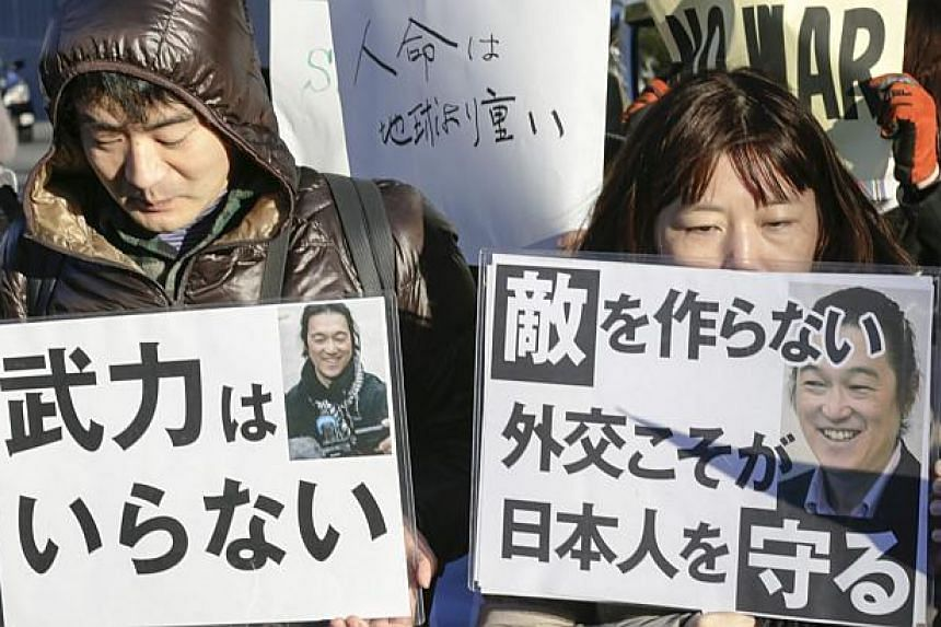 Mourning demonstrators hold a silent prayer rally and protest against Japanese Prime Minister Shinzo Abe's behavior and the murder of hostages held by Islamic State in Iraq and Syria (ISIS) militants, in Tokyo, on Feb 1, 2015.Tokyo on Monday, F
