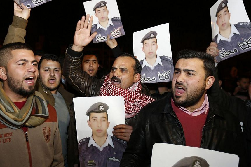 Relatives of captured pilot Muath al-Kasaesbeh holding up his pictures in front of the Jordanian prime minister's building in Amman on Jan 27 as they called for the government to negotiate with ISIS for his release. The militant group later released