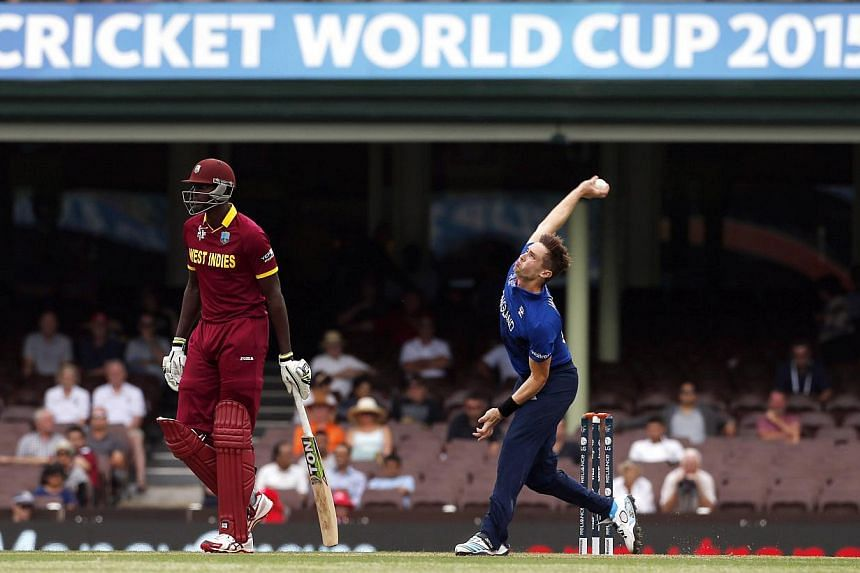 Chris Woakes (right) of England bowls next to Lendl Simmons of the West Indies during their warm-up match at the Sydney Cricket Ground on Feb 9, 2015.Chris Woakes took five for 19 as England claimed a comfortable nine-wicket victory in their fi